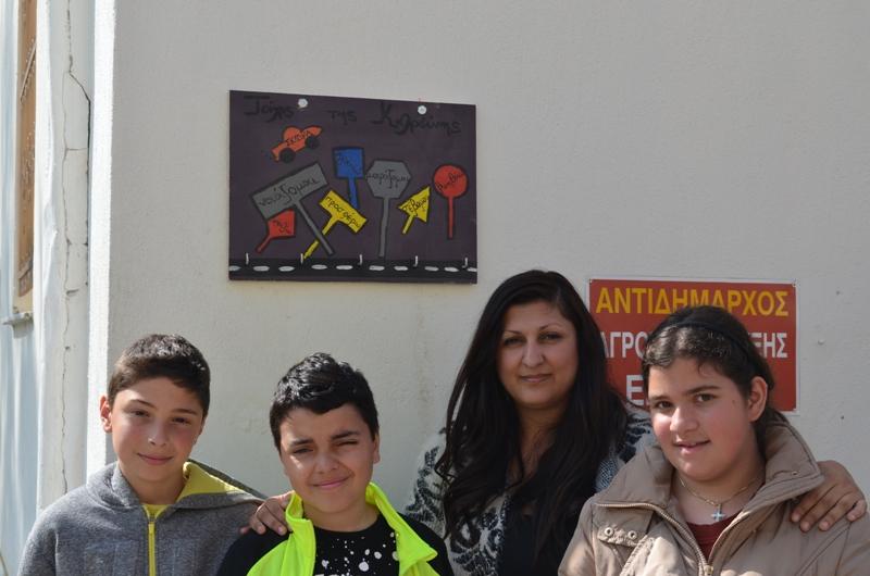 Η κοινωνική λειτουργός με παιδιά, μπροστά από την κρεμάστρα του τοίχου του Δημαρχείου